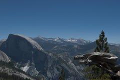 Mening over vallei vanaf de bovenkant van de berg en de pieken van mauntains door het pijnboombos royalty-vrije stock afbeelding