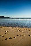 Mening over zandig strand met voetensporen en de Atlantische Oceaan met blauwe hemel in zonsondergang Stock Foto's