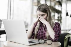 Mening tröttat och stressat Den frustrerade unga kvinnan som håller ögon, stängde sig och masserar näsan, medan sitta på hennes a Arkivbild