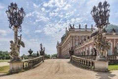 Mening van één van de ingangen van Das Neue Palast met zijn barokke standbeelden, smeedijzerlantaarns, en een deel van de paleist Stock Afbeeldingen