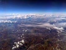 Mening van aarde van een vliegtuig met Europees berglandschap met rivieren en sneeuw met verspreide witte wolken en donkerblauwe  stock afbeelding