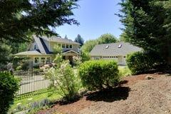 Mening van aardig huis met bloeiende struiken stock afbeelding