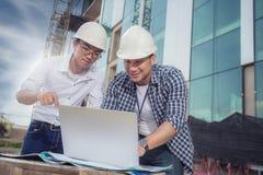 Mening van arbeiders en architecten die details over constructio zien Stock Fotografie