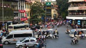 Mening van bezig verkeer in een kruising met vele motoren en voertuigen in Hanoi, hoofdstad van Vietnam stock video