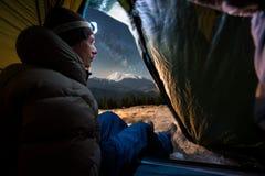 Mening van binnenuit een tent op de mannelijke toerist die in zijn het kamperen bij nacht genieten van Royalty-vrije Stock Fotografie