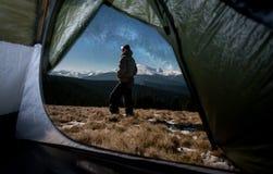 Mening van binnenuit een tent op de mannelijke toerist in zijn het kamperen in de bergen bij nacht Stock Foto's