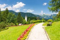 Mening van Bohinj-kerk in het dorp van Ribcev Laz, van het park met standbeeld Triglav en bergen op de achtergrond, park met gras stock afbeeldingen