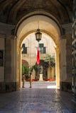 Mening van boogingang van Grandmaster-Paleisbinnenplaats met Maltese vlag en militair twee in Valletta stock fotografie