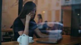 Mening van buiten een aantrekkelijke jonge vrouw die op de telefoon in een koffie spreken en het scherm van haar bekijken stock footage