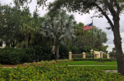 Mening van de Amerikaanse vlag met sterren en strepen voor de palmen op een groen gazon onder een blauwe hemel met wolken in Nape Stock Foto's