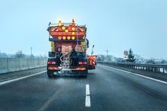 Mening van de auto achter de oranje vrachtwagen van het wegonderhoud royalty-vrije stock fotografie