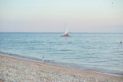 Mening van de baai, het zandige strand en het zeil royalty-vrije stock afbeeldingen