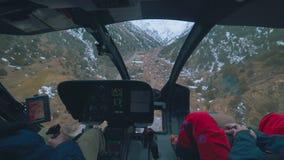 Mening van de binnenkant van een helikopter die over bergen naderbij komen stock footage