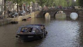 Mening van de brug van zich het bewegen op het kanaalschip met mensen, Amsterdam, Nederland stock footage