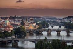 Mening van de bruggen van Praag met oranje hierboven hemel van Stock Fotografie