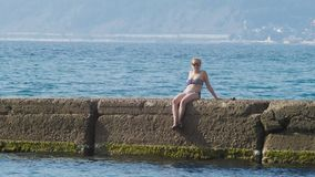 Mening van de eilanden in de baai Telephotoschot de vrouw op de golfbreker bekijkt de kust in de mist, langzaam 4k, stock videobeelden