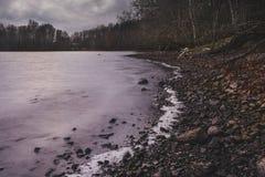 Mening van de de herfst de donkere oever van het meer met een boot Royalty-vrije Stock Afbeelding