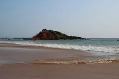 Mening van de heuvel in het midden van het zandige strand stock fotografie