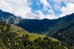 Mening van de himalayan die piek met sneeuw en klein Indisch dorp in het bos wordt behandeld royalty-vrije stock fotografie