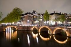 Mening van de de kanalen en dijken van Amsterdam langs hen bij nacht Royalty-vrije Stock Afbeelding