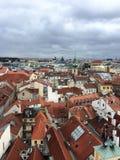 Mening van de klokketoren van Praag aan de beroemde rode daken stock fotografie