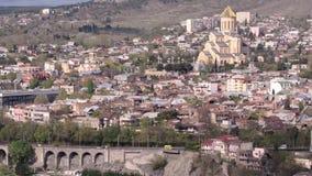 Mening van de lente van Tbilisi, de brug met de machines en de Kathedraal van Heilige Drievuldigheidskathedraal van Tbilisi APRIL stock footage
