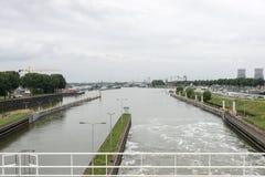 Mening van de maas riviersluis bij de stadshorizon maasbracht Stock Afbeeldingen