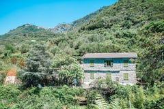 Mening van de ??n oude bouw tegen een majestueus berglandschap en Italiaanse wijngaarden in Cinque Terre stock fotografie