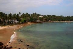 Mening van de oceaan en zandige kust met palmen royalty-vrije stock afbeeldingen