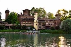 Mening van de overkant die van het Valentino-kasteel, de bezinning van de zon op het water en verscheidene kanovaarders op de riv Stock Foto's