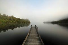 Mening van de pier bij een nevelig meer in Nieuw Zeeland Stock Afbeelding