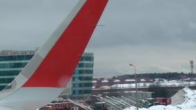 Mening van de rode vleugel die van het vliegtuigvenster zich door luchthavenbaan bewegen, close-upschot, stock footage