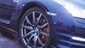 Mening van de schijf van het wielenijzer van donkerblauwe nieuwe auto presentatie koplamp Zon auto Koude schaduwen stock videobeelden