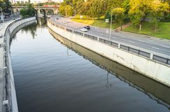 Mening van de spiegeloppervlakte van de Yauza-rivier en de rijweg van zijn dijk in zonsonderganglicht, Moskou royalty-vrije stock fotografie