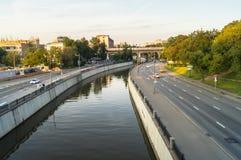 Mening van de spiegeloppervlakte van de Yauza-rivier en de rijweg van zijn dijk in zonsonderganglicht, Moskou royalty-vrije stock afbeeldingen