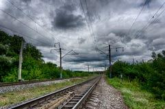 Mening van de spoorweg die in de afstand door de bomen achteruitgaan royalty-vrije stock fotografie