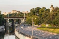 Mening van de spoorwegbrug over de Yauza-rivier en de rijweg van zijn dijk in zonsonderganglicht, Moskou stock foto