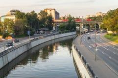 Mening van de spoorwegbrug over de Yauza-rivier en de rijweg van zijn dijk in zonsonderganglicht, Moskou stock afbeelding