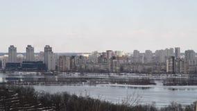 Mening van de stad en onroerende goederen door de de winterrivier in het ijs stock videobeelden
