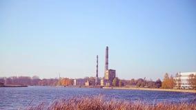 Mening van de stadsrand met industriezone en fabriekspijpen door de rivier stock video