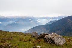 Mening van de vallei in himalayan die bergen met wolken worden behandeld royalty-vrije stock foto
