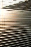 Mening van de verlichte het plaatsen zonzonneblinden Stock Foto
