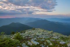 Mening van de zonsondergang van de bergen in de afstand De donkere silhouetten van de pieken van de bergen, Royalty-vrije Stock Foto's