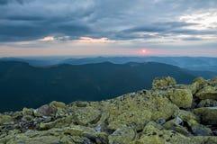 Mening van de zonsondergang van de bergen in de afstand De donkere silhouetten van de pieken van de bergen, reusachtige blokken v Royalty-vrije Stock Foto's