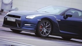 Mening van donkerblauw nieuw autoverblijf op straat wielen presentatie koplampen auto Koude schaduwen stock videobeelden