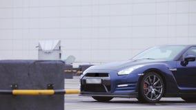 Mening van donkerblauwe nieuwe autotribune op leeg parkeren Presentatie nieuw model koplampen Koude schaduwen stock video
