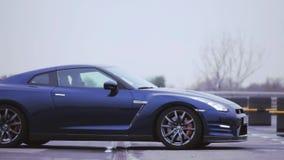 Mening van donkerblauwe nieuwe coupéauto Wielenschijven presentatie showing Luxeauto Koude schaduwen stock video