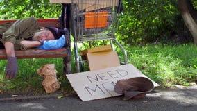 Mening van dronken dakloze mensenslaap in dagtijd op de bank in de straat stock videobeelden