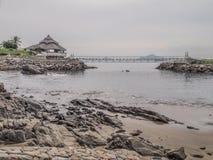 Mening van een baai met zijn strand met rotsen met een terras op rotsen een brug met het overzees op de achtergrond stock foto