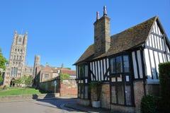 Mening van een betimmerd ontworpen en middeleeuws huis in Ely het UK met het het Westendeel van de Kathedraal op de achtergrond stock afbeelding